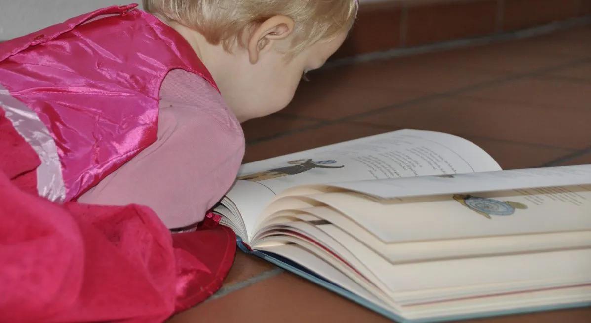 Menina lendo livro no chão. Imagem ilustrativa texto leitura e inteligência.
