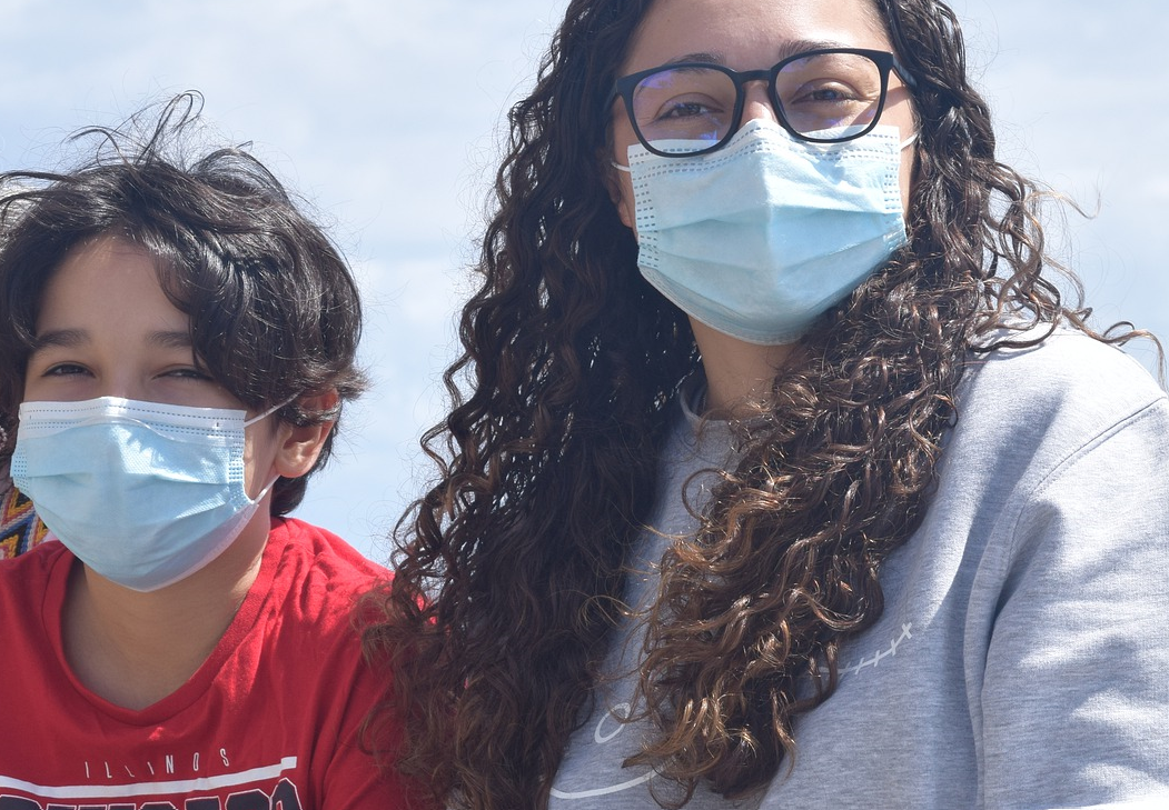 Mãe e filho de máscara ao ar livre. Imagem ilustrativa texto férias de julho.