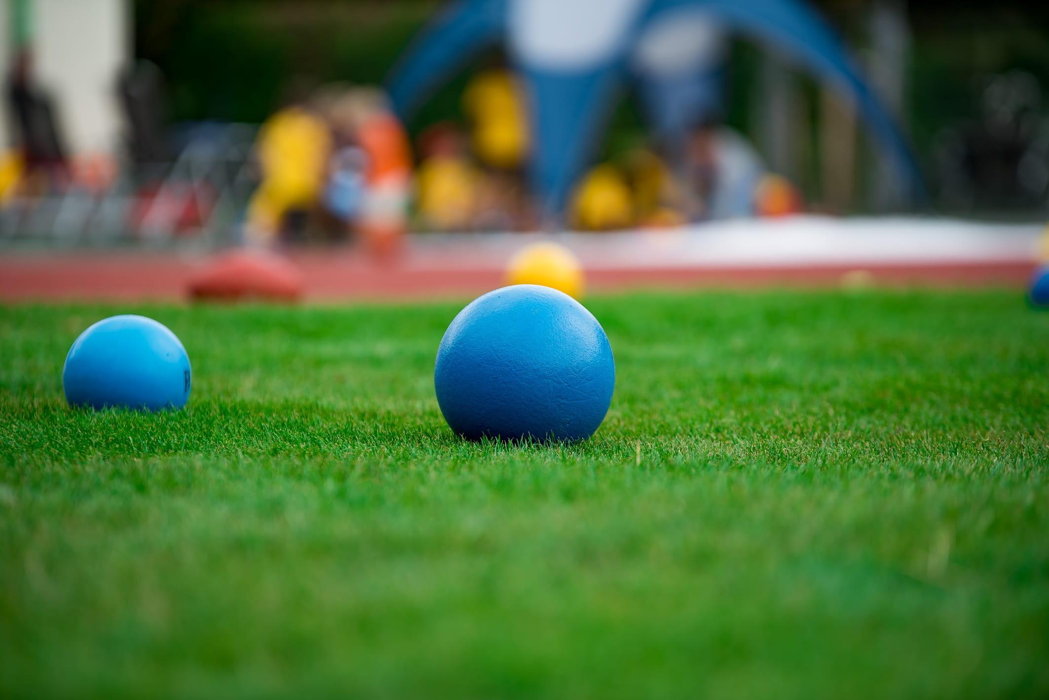 Bolas azuis na grama. Imagem ilustrativa texto olimpíada em casa.