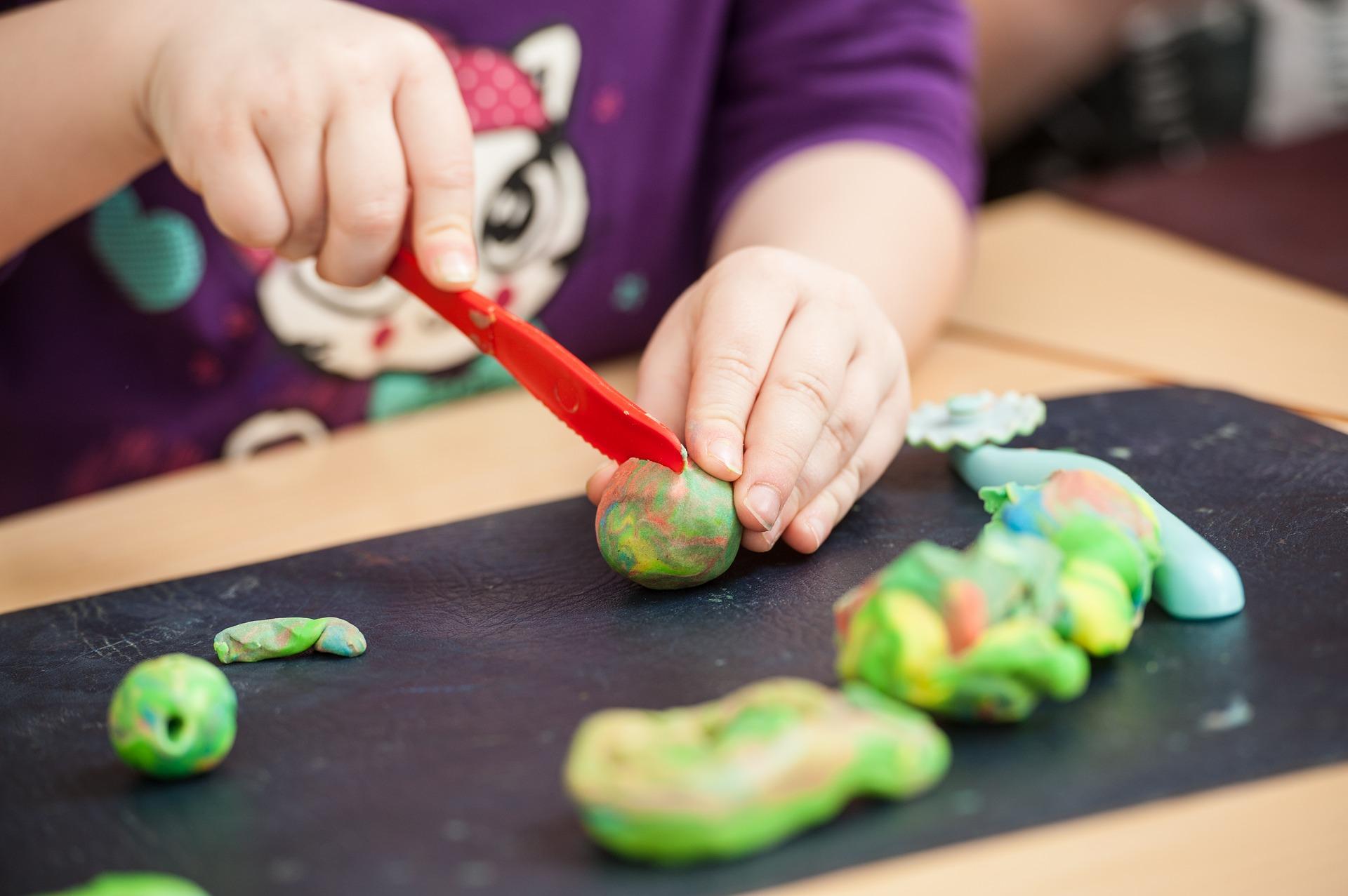 Mãos de criança brincando com faca de plástico e massa de modelar. Imagem ilustrativa texto como fazer massinha.