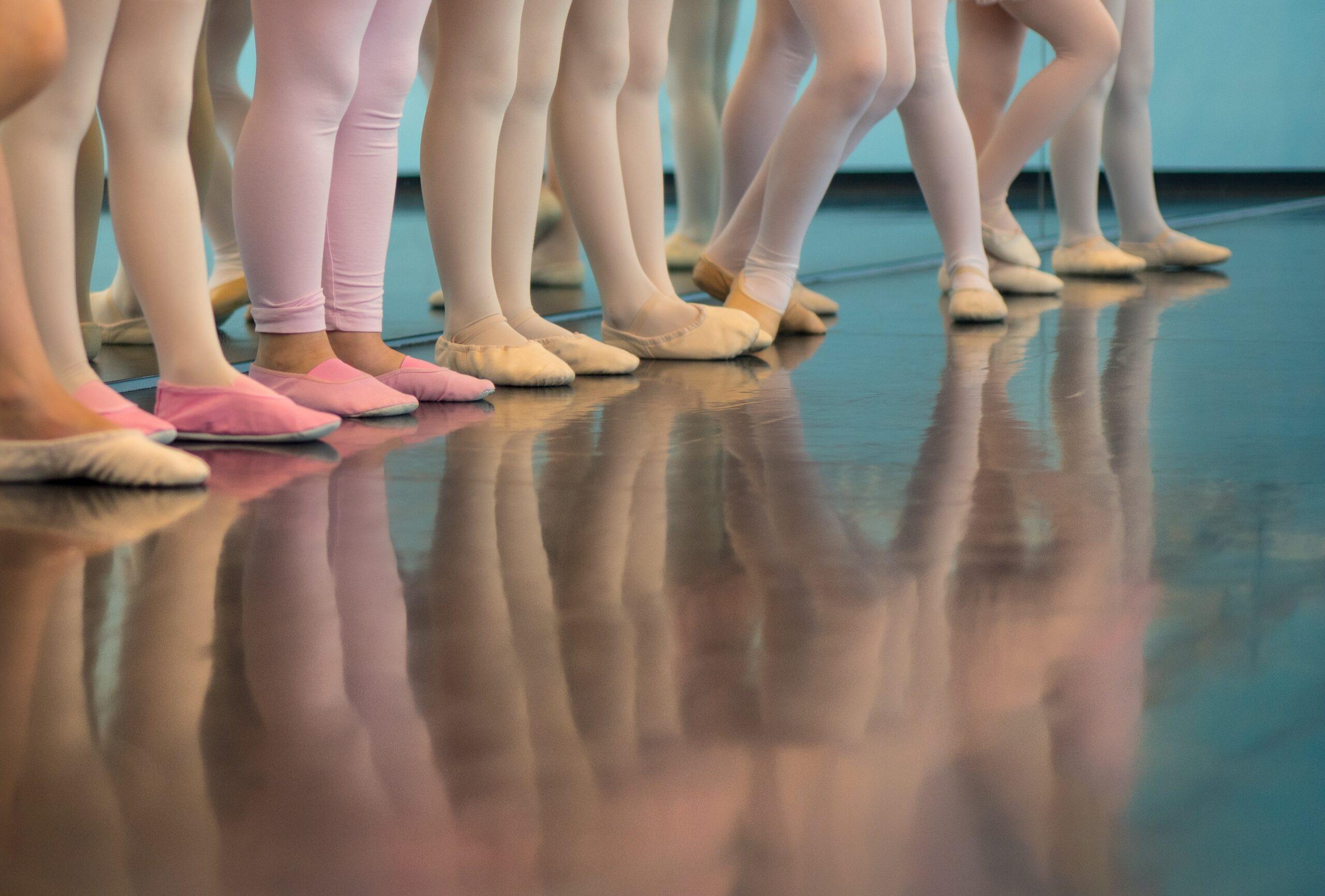 Pés de meninas na aula de balé. Imagem ilustrativa texto iniciar as crianças na dança.