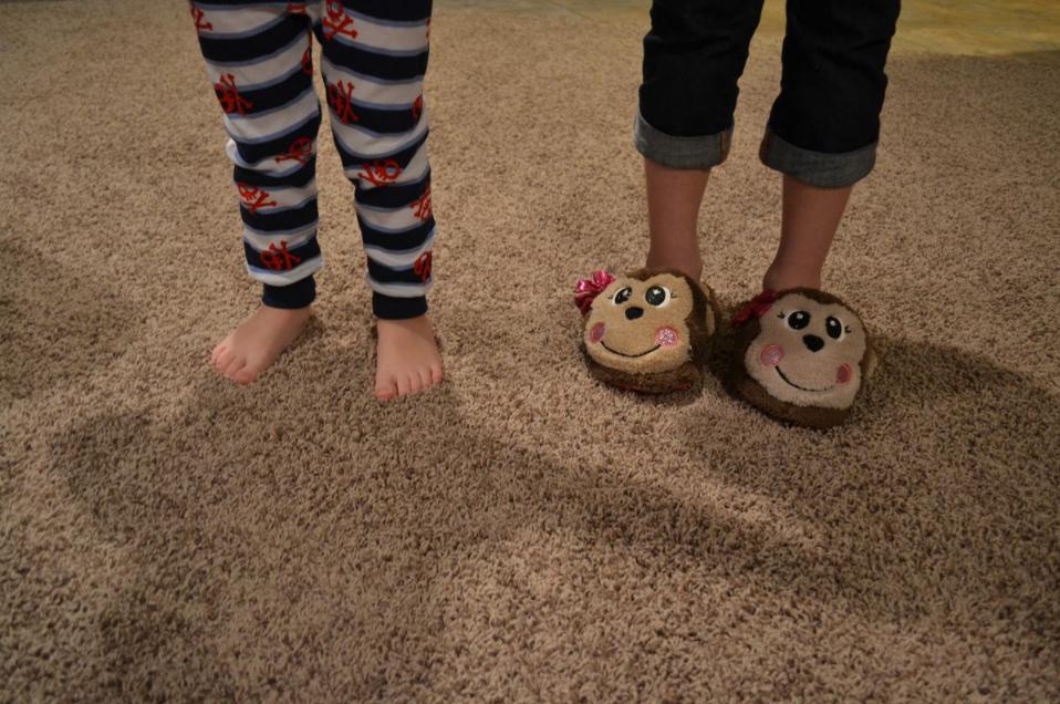 Menino descalço de pijama e menina com pantufa de macaco no chão acarpetado. Imagem ilustrativa texto dormir na cama dos pais.