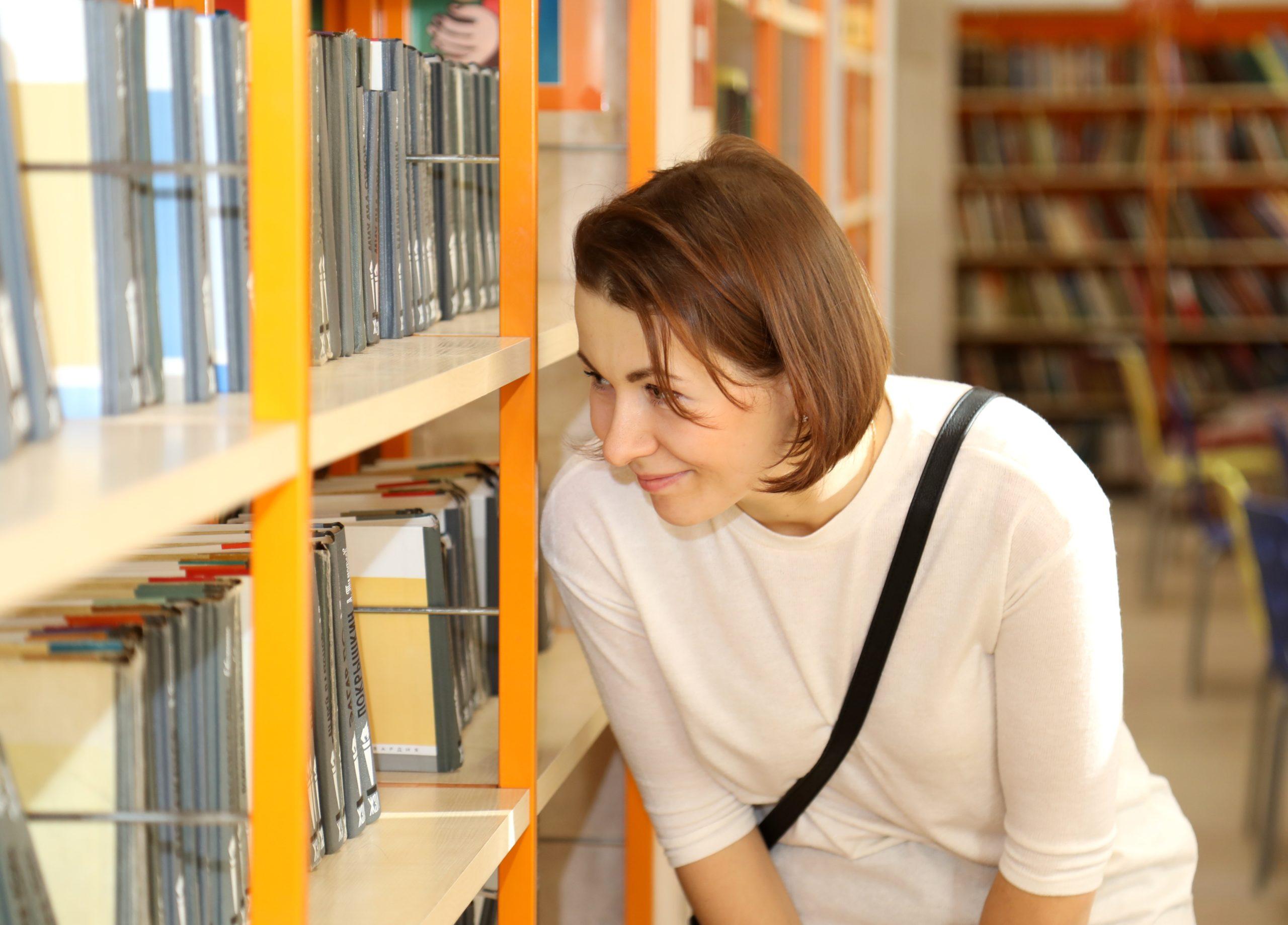 Mulher olhando livros na prateleira. Imagem ilustrativa texto Dia Internacional da Mulher.