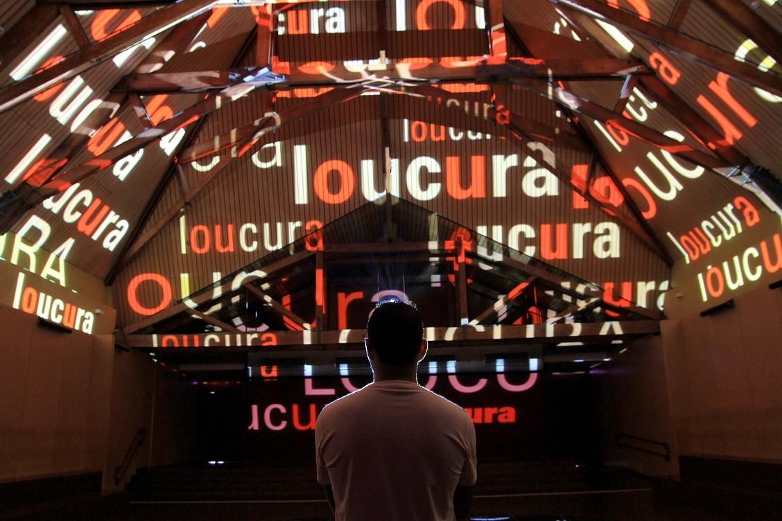 A palavra loucura projetada diversas vezes na parede, com homem olhando. Imagem ilustrativa texto Museu da Língua Portuguesa.