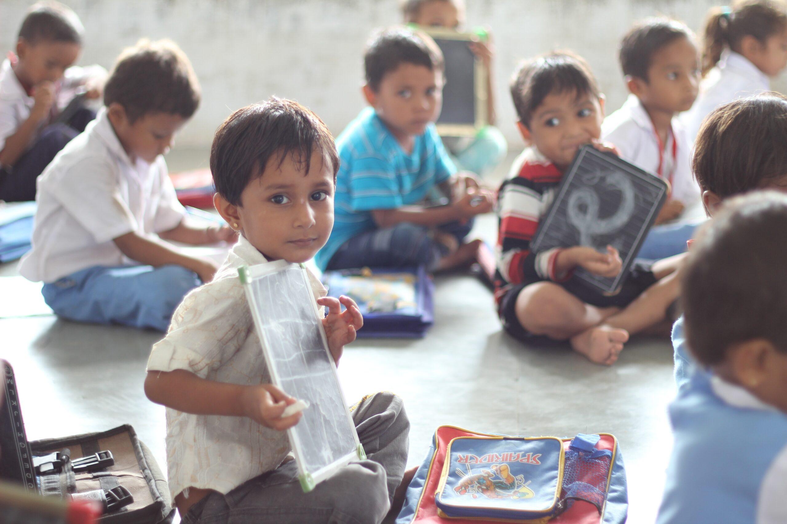 Crianças sentadas no chão, mostrando desenho. Imagem ilustrativa texto desafios da educação infantil.