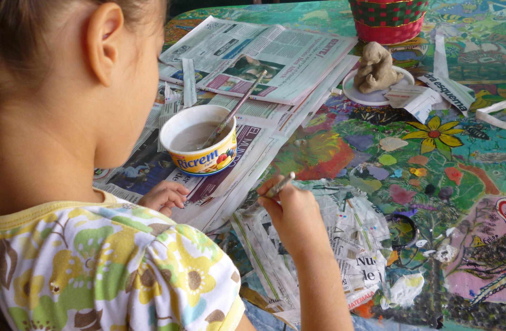 Menina pintando, com jornais no chão. Imagem ilustrativa texto formas de arte.