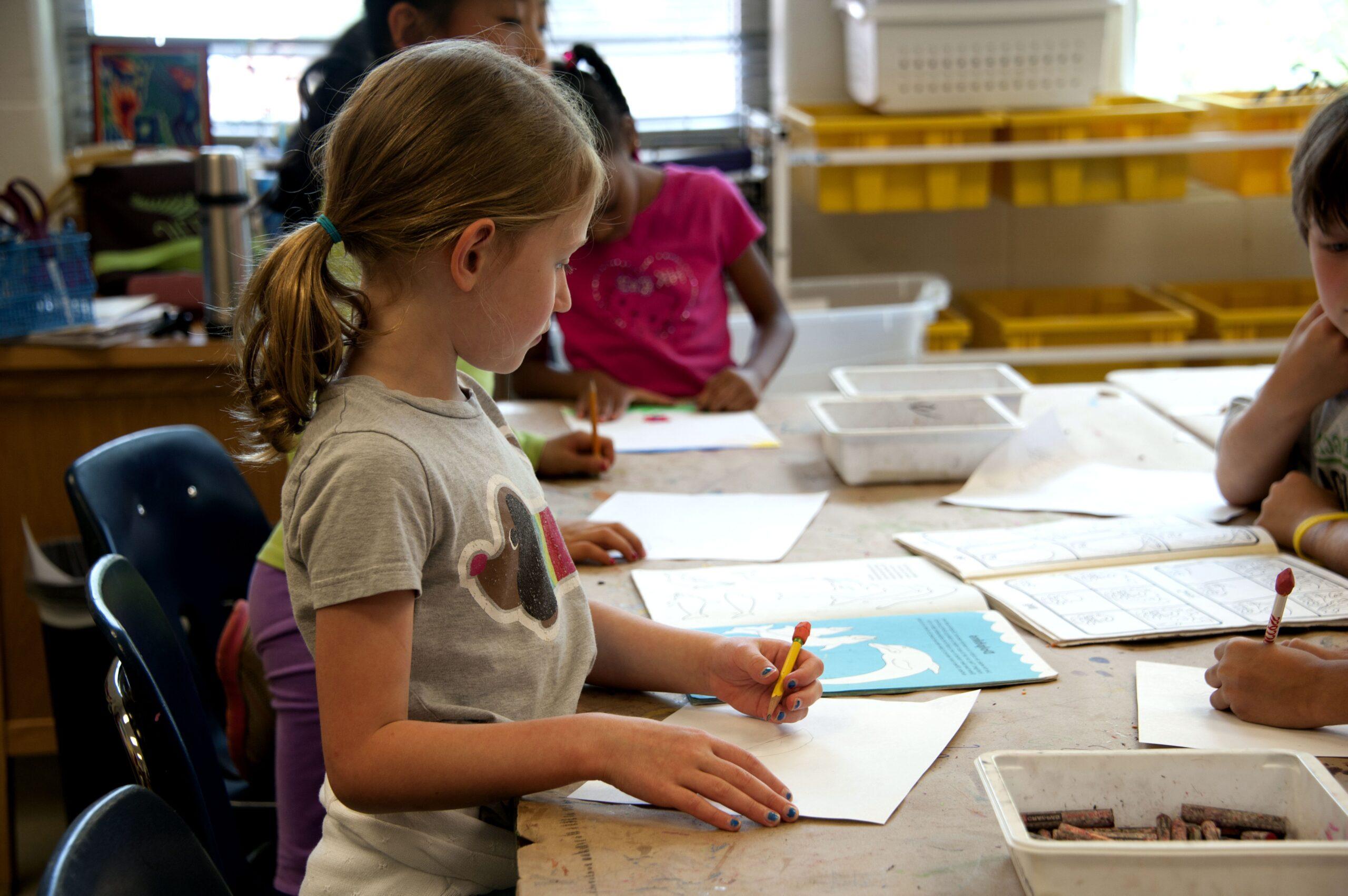 Menina desenhando na escola, com outras crianças. Imagem ilustrativa texto criar histórias em quadrinhos.